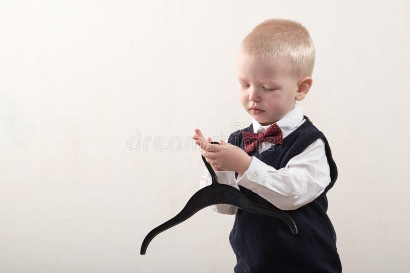 在家使用愉快的男孩 巧妙的衣裳和一个挂衣架在手上 免版税库存照片