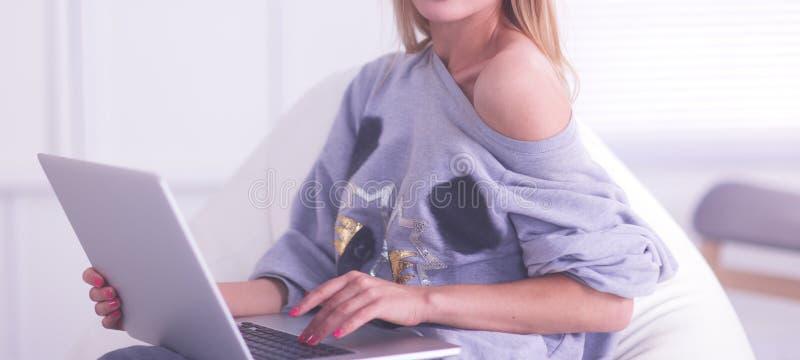 在家使用手提电脑的年轻美女 免版税库存照片