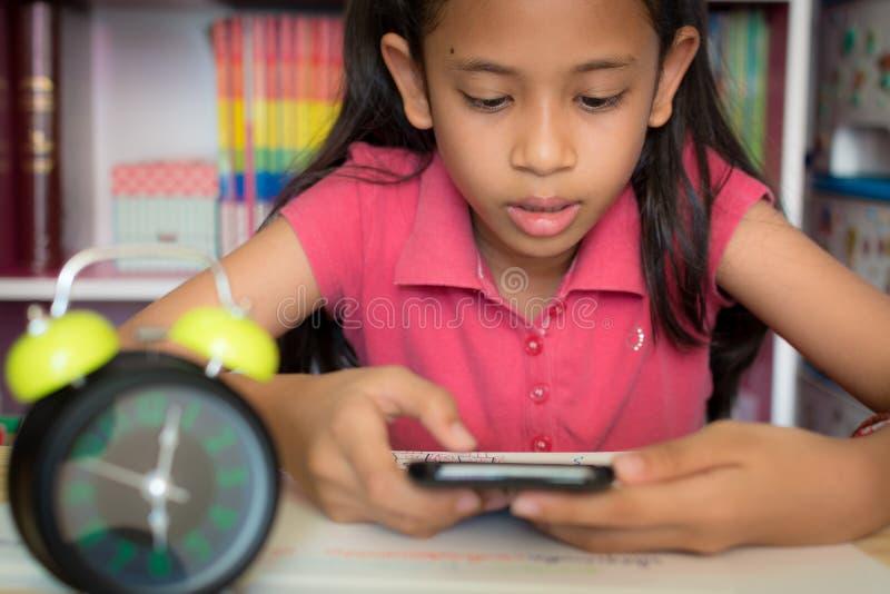 在家使用手机的小女孩 免版税图库摄影