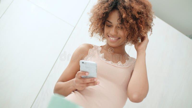 在家使用手机的美丽的年轻美国黑人的妇女 免版税库存图片