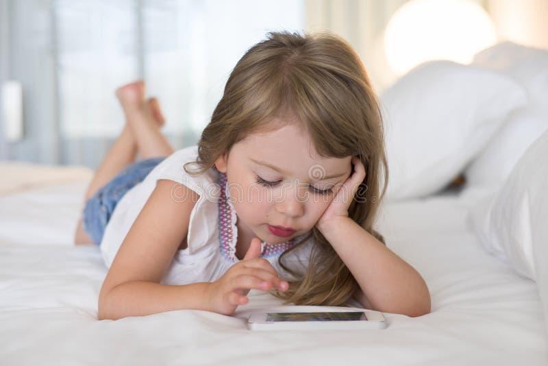 在家使用手机的逗人喜爱的小女孩 图库摄影
