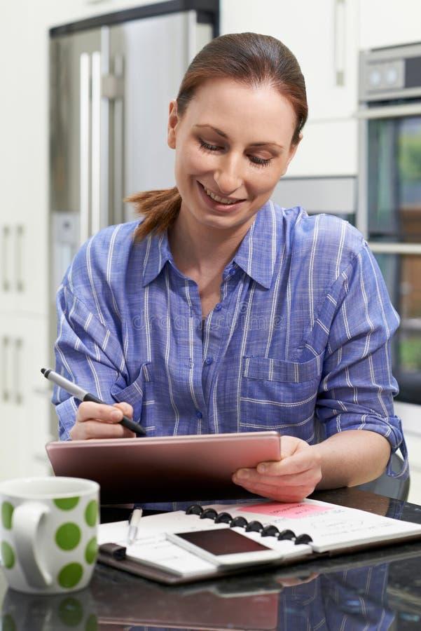 在家使用数字式图形输入板的女性自由职业者的工作者 库存图片