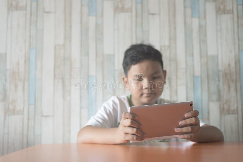 在家使用数字式片剂的年轻亚裔男孩在片剂的餐桌焦点 免版税库存图片