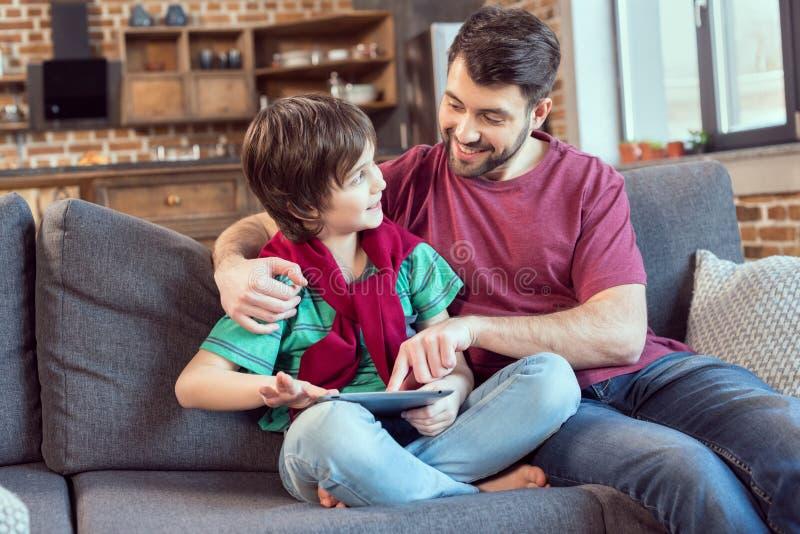 在家使用数字式片剂的父亲和儿子 库存图片