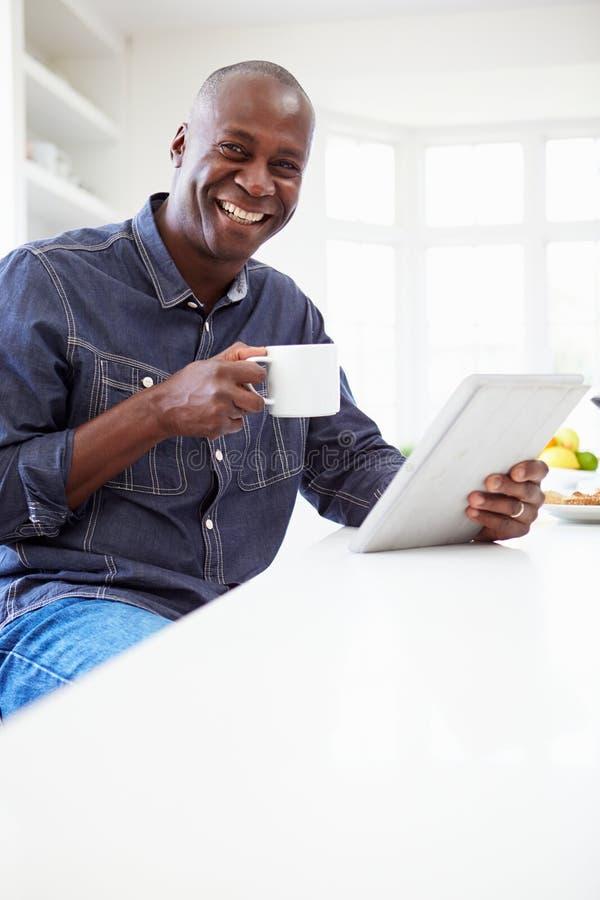 在家使用数字式片剂的非裔美国人的人 免版税库存图片