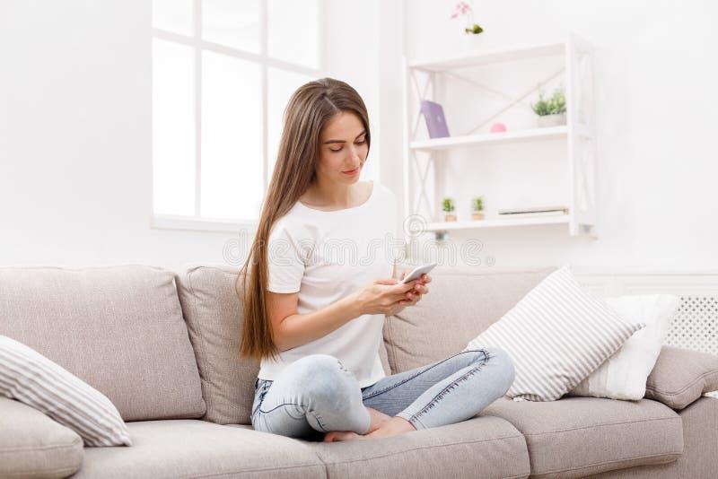 在家使用智能手机在长沙发的少妇 偶然在网上发短信的深色头发的女孩 免版税库存图片