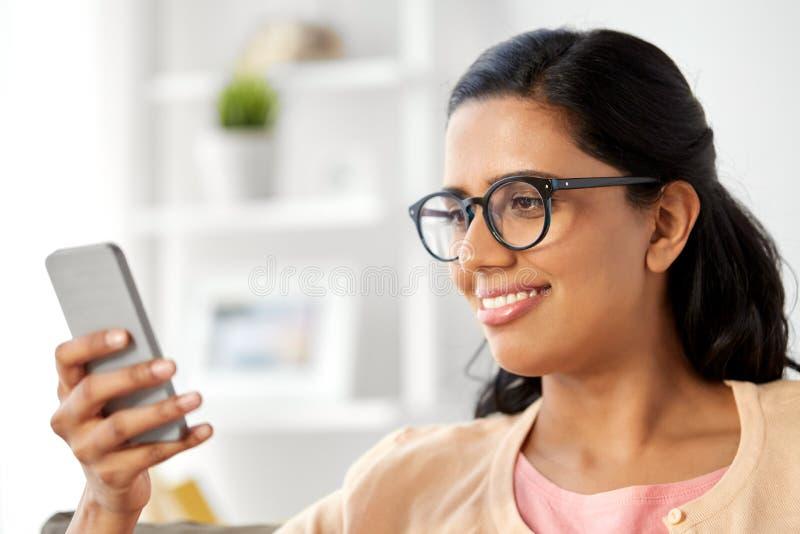 在家使用智能手机的愉快的印度妇女 免版税库存图片