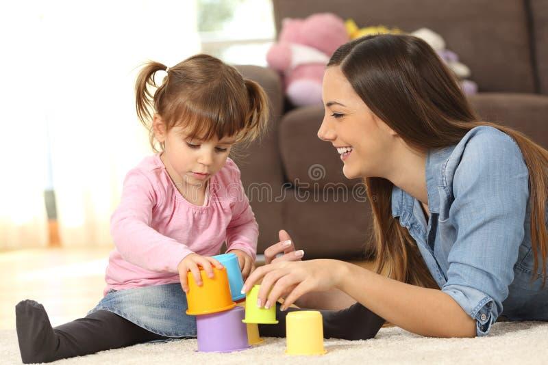 在家使用母亲和小的女儿 免版税图库摄影