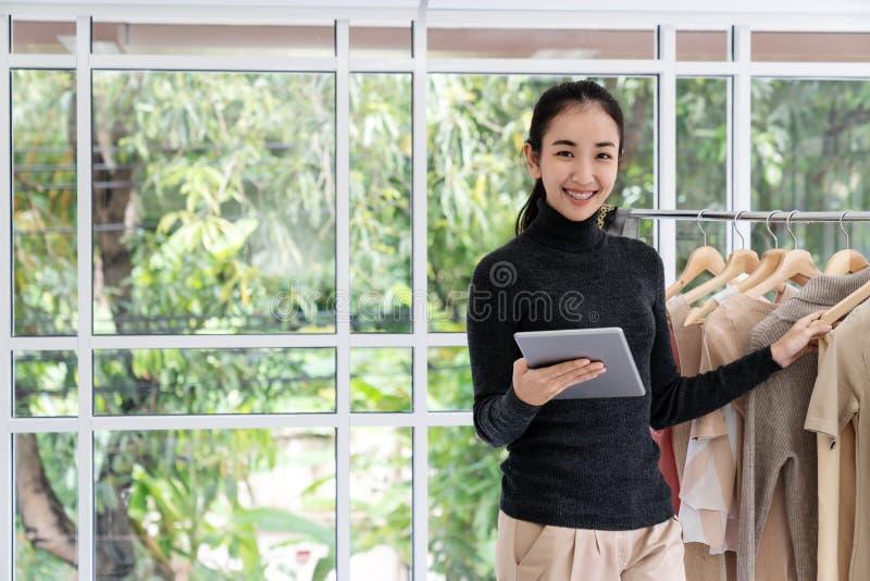 在家使用片剂工作办公室的年轻亚裔企业家妇女看与愉快的偶然生活方式的照相机 免版税库存图片