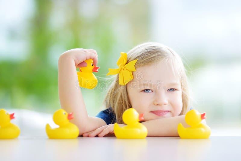 在家使用用橡胶鸭子的逗人喜爱的小女孩 库存照片