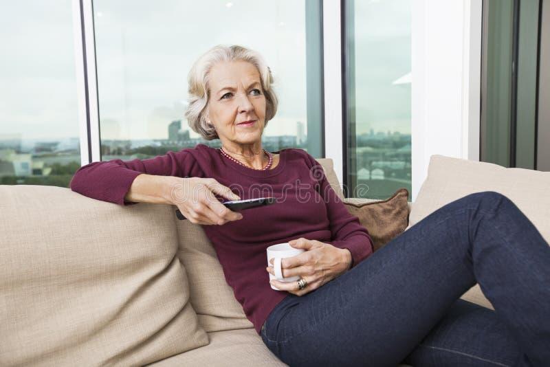 在家使用电视的资深妇女遥控在沙发 免版税库存照片