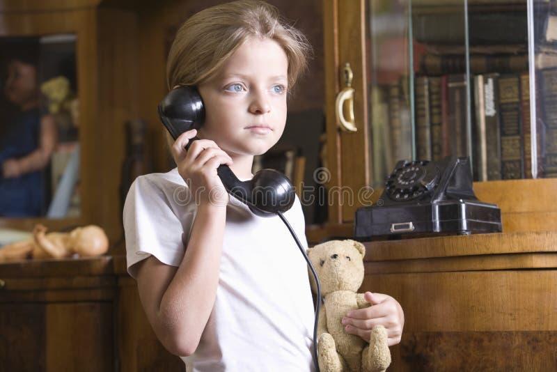 在家使用电话的女孩 图库摄影