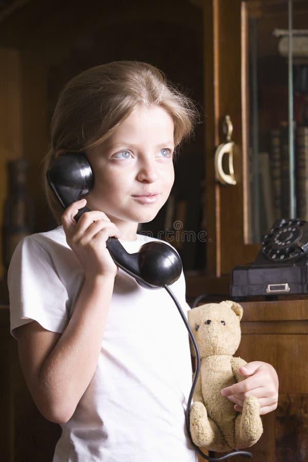 在家使用电话的女孩 免版税图库摄影