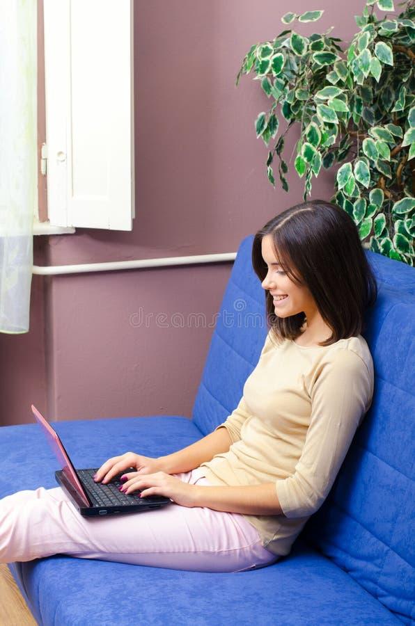 在家使用笔记本的美丽的微笑的十几岁的女孩 库存照片