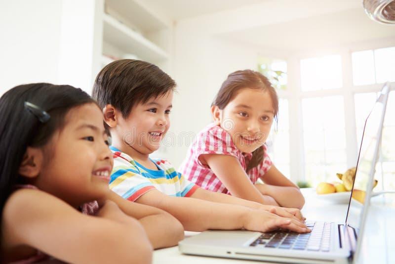 在家使用膝上型计算机的三个亚裔孩子 免版税库存照片