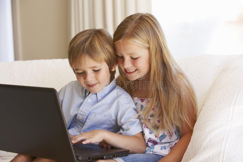 在家使用膝上型计算机的两个幼儿 库存图片
