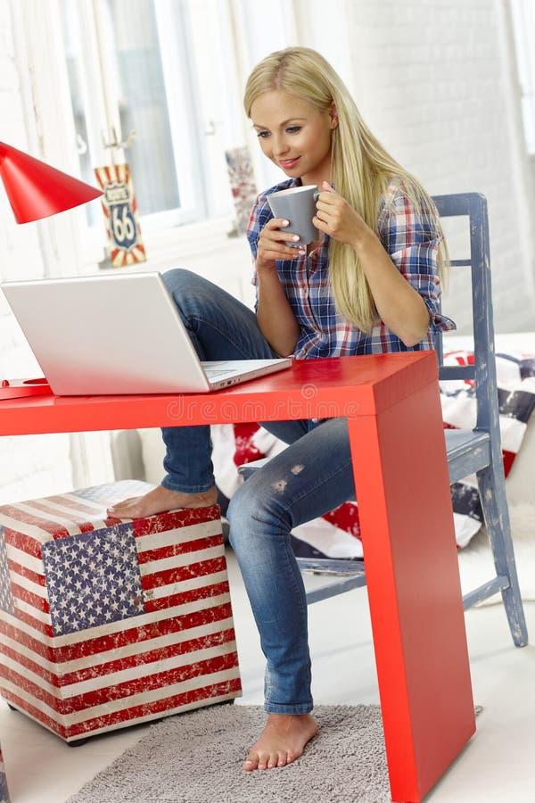 在家使用膝上型计算机的偶然妇女 免版税库存照片