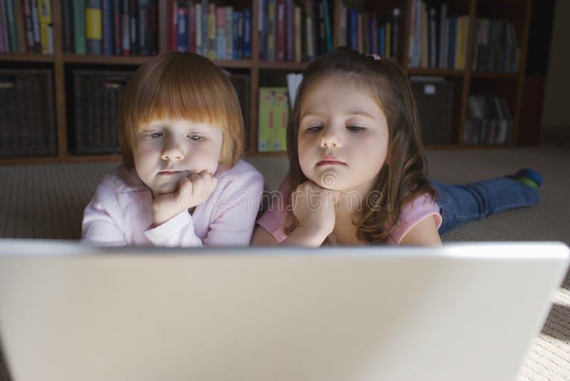 在家使用膝上型计算机的好奇女孩 图库摄影
