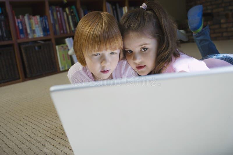 在家使用膝上型计算机的好奇女孩 免版税图库摄影