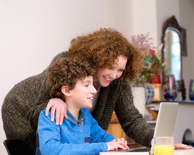 在家使用膝上型计算机的愉快的母亲和儿子 免版税库存照片