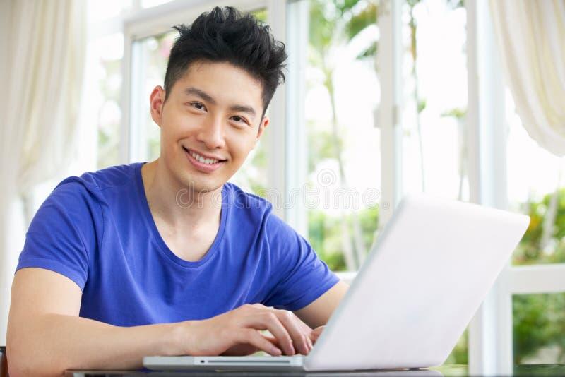 在家使用膝上型计算机的担心的新中国人 免版税库存照片