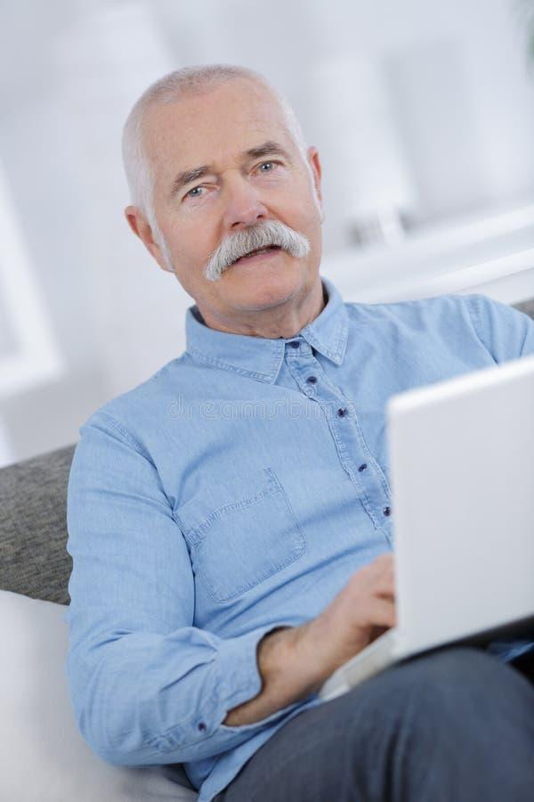 在家使用膝上型计算机的画象老人 免版税库存图片