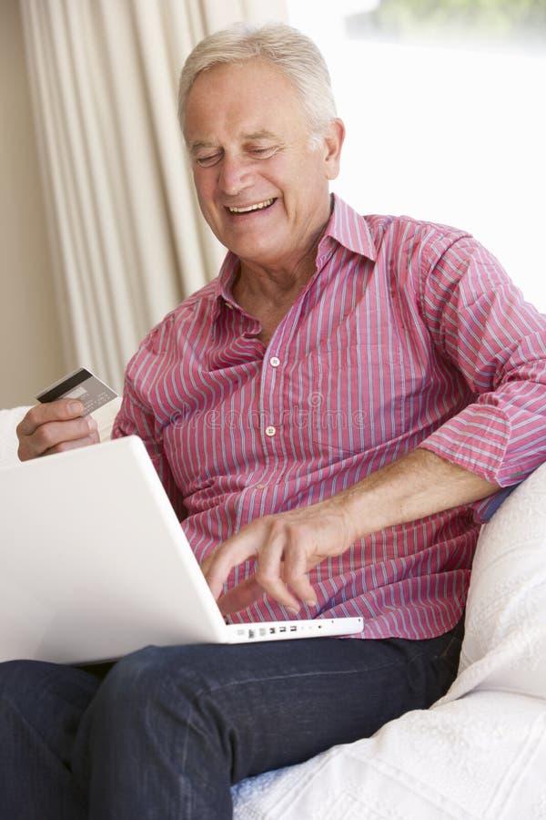 在家使用膝上型计算机的老人为网上购买 免版税库存图片