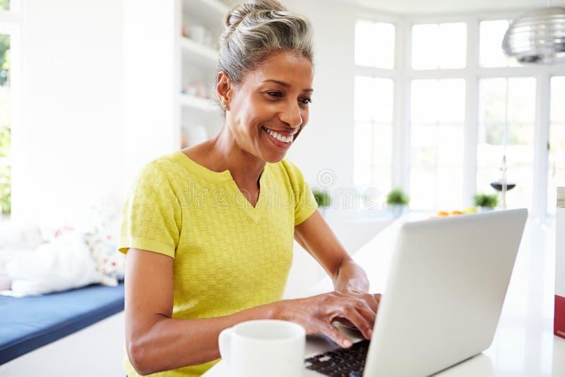 在家使用膝上型计算机的非裔美国人的妇女在厨房 免版税库存图片
