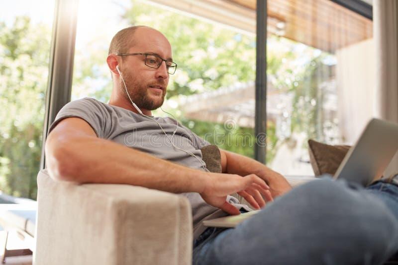在家使用膝上型计算机的轻松的成熟人 免版税库存照片