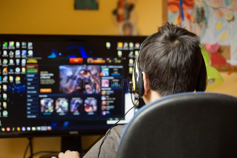 在家使用计算机的男孩,打比赛 免版税库存图片