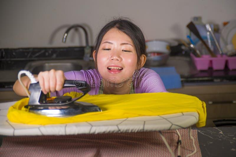 在家使用铁厨房电烙的衣裳的年轻俏丽和愉快的亚裔韩国妇女微笑快乐和无忧无虑享用domest 免版税库存照片