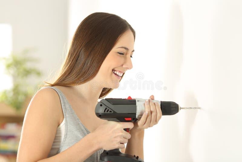 在家使用钻子的女孩在墙壁 库存照片