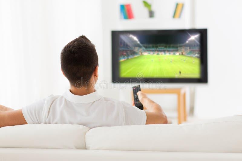 在家供以人员在电视的观看的橄榄球赛从后面 免版税库存照片