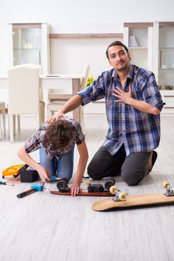 在家修理与他的儿子的年轻父亲滑板 免版税图库摄影
