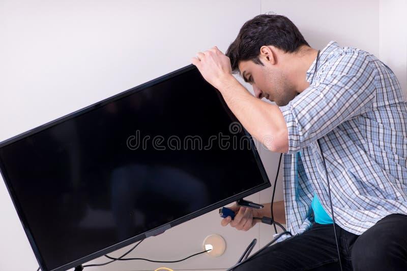 在家修理打破的电视的人 免版税库存照片