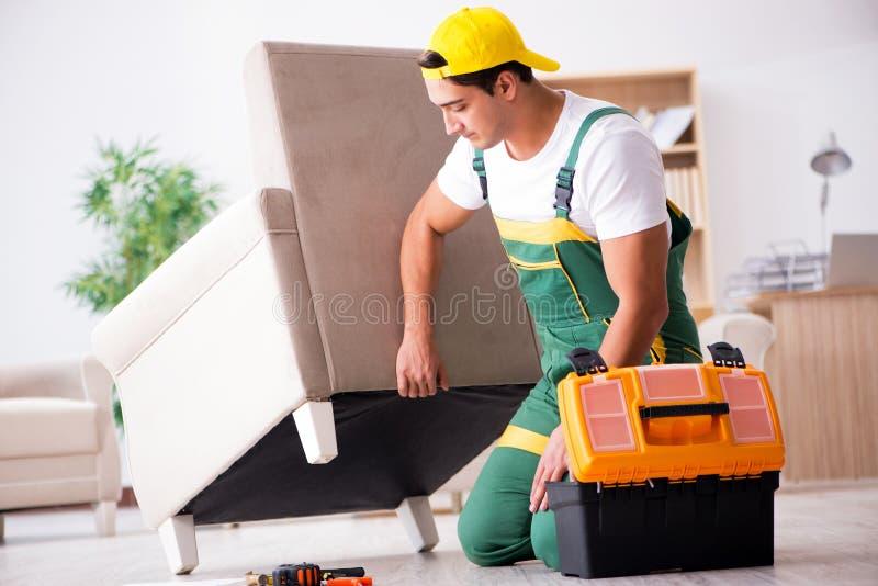 在家修理扶手椅子的家具安装工 免版税库存图片