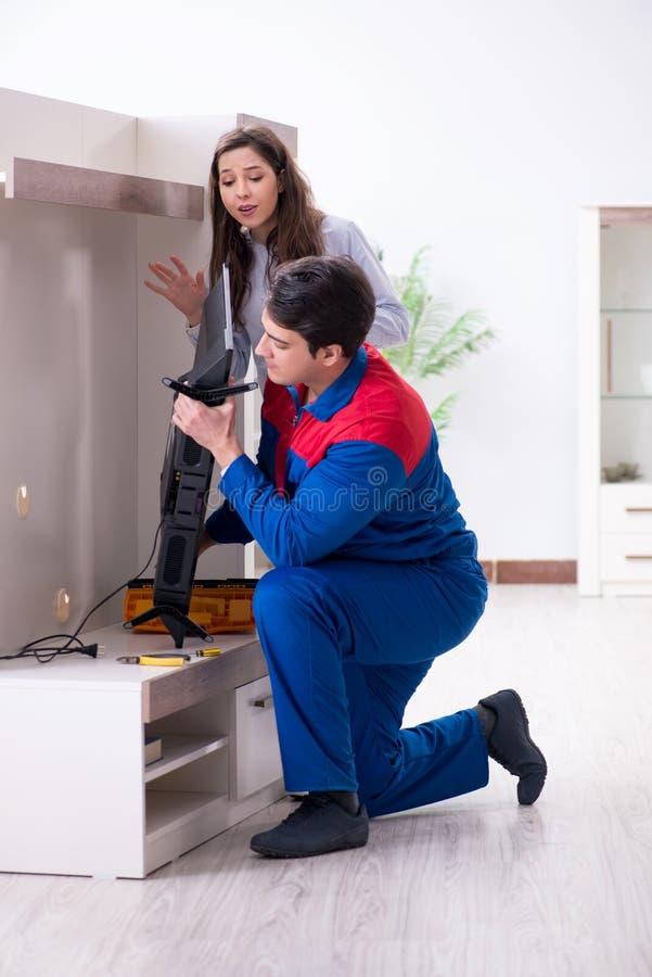 在家修理电视的电视安装工技术员 图库摄影