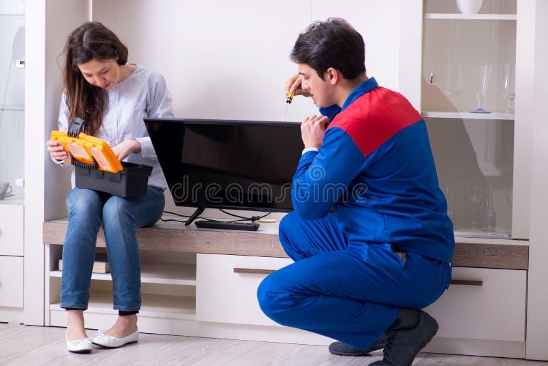 在家修理电视的电视安装工技术员 免版税库存照片