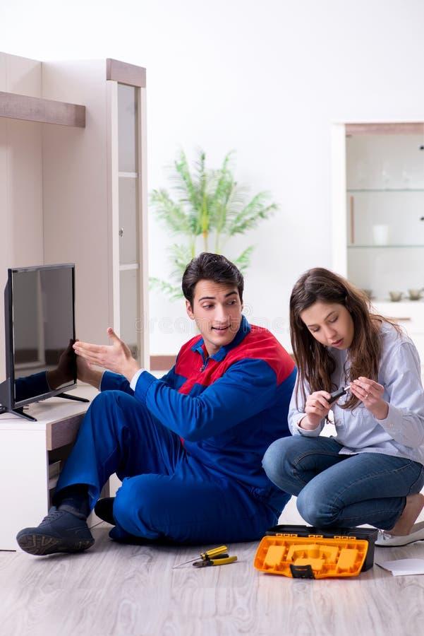在家修理电视的电视安装工技术员 免版税库存图片