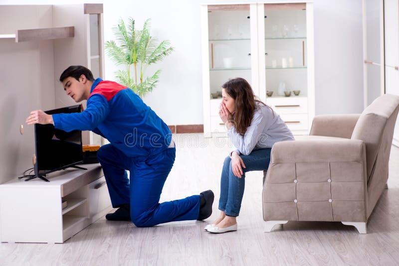 在家修理电视的电视安装工技术员 库存照片