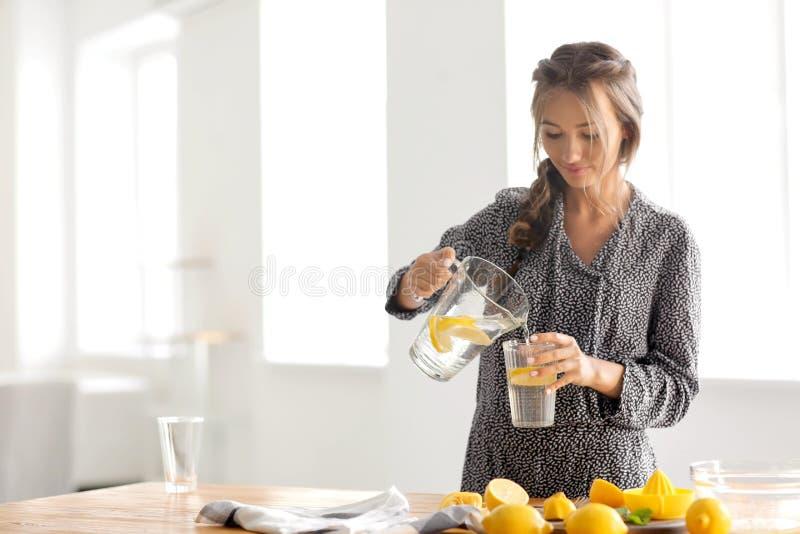 在家倒从水罐的年轻女人新鲜的柠檬水入玻璃 免版税图库摄影