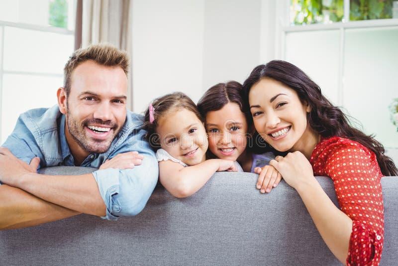 在家倾斜在沙发的愉快的家庭 库存照片