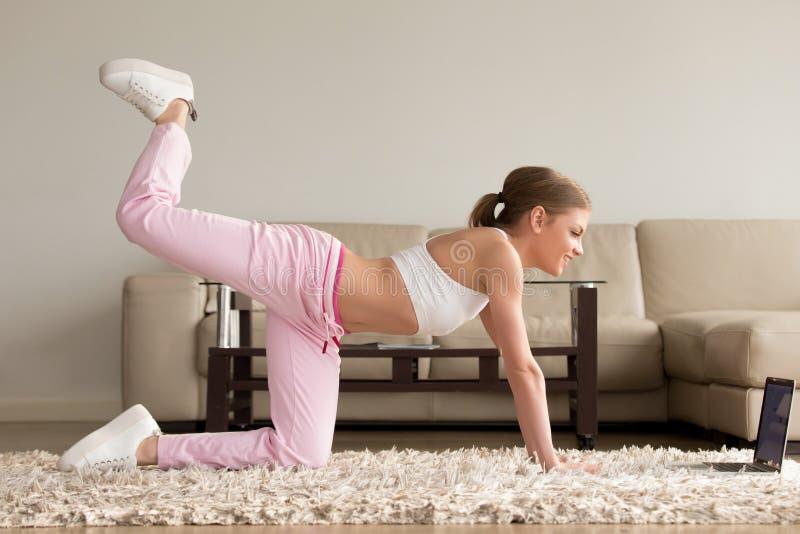 在家做一膝盖佣金锻炼的妇女 免版税库存图片