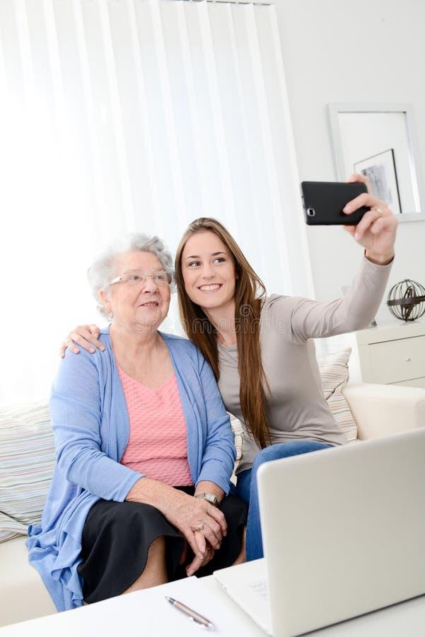 在家做与她的年轻孙女的年长妇女selfie 免版税库存照片