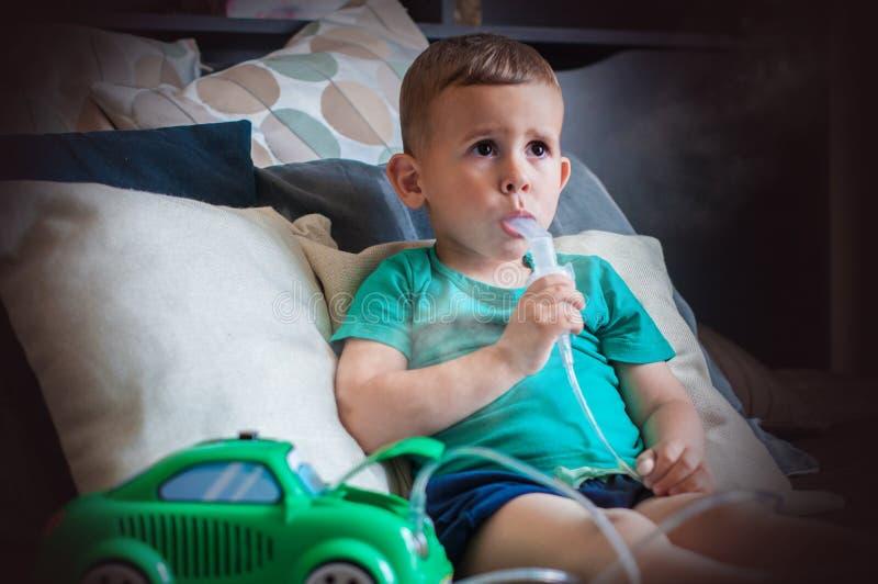 在家做与雾化器的三岁的男孩吸入 免版税图库摄影