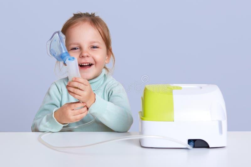 在家做与雾化器的女孩吸入,孩子遭受哮喘,用途吸入器,坐在白色桌面,看 免版税库存照片