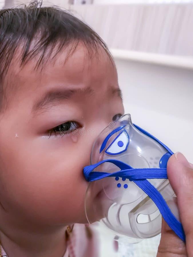 在家做与雾化器的女孩吸入 儿童哮喘吸入器吸入雾化器蒸汽病态的咳嗽概念 库存照片
