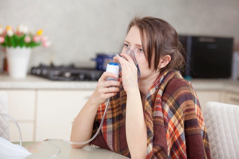 在家做与雾化器的年轻女人吸入 免版税库存照片