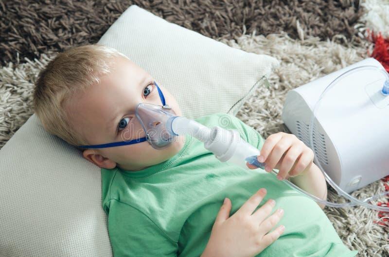 在家做与雾化器的男孩吸入 库存照片
