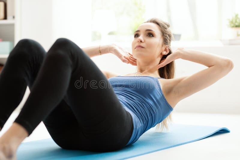 在家做仰卧起坐在地板上的适合妇女 免版税库存照片